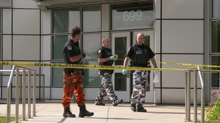 lieutenant : Police officer unroll crime tape around police station Police officers wearing camo pants as a mean of protest are locking down a police station with yellow crime tape