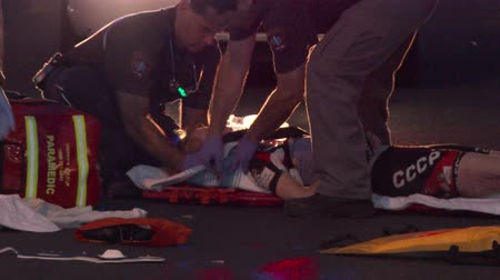 ambulância : Female cyclist with critical injuries after struck by car Firemen and paramedic provide first aid to female cyclist lying down on street after being violently struck and run over by car.