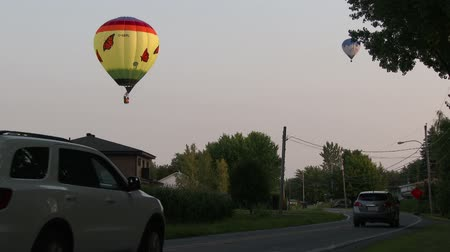 bolsa : 4K UHD - 60fps or 30fps - Hot air balloon flying above country road with cars Stock Footage