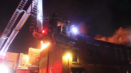 égés : Firemen in elevated basket rise above heavy flames of building fire  - Commercial license no logo no face