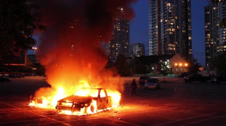 Police cars burning in parking lot with riot officer and residential buildings  Stock Footage
