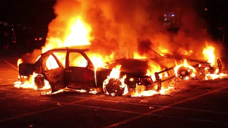 car logo : Two burning cars at night with rioters and swat officer in background  - Commercial license no logo no face
