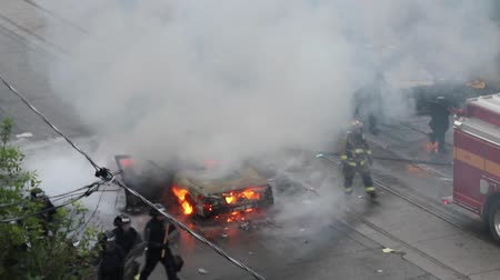 car logo : Riot officers and fireman walking around car fire with smoke  - Commercial license no logo no face Stock Footage