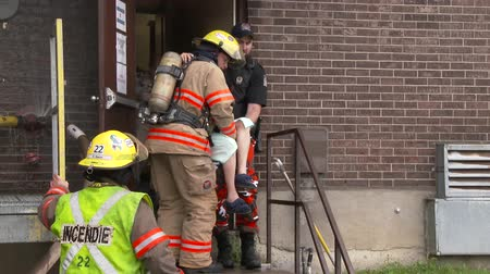 4K UHD - Fireman and policeman rescuing elderly woman out of building Stock Footage