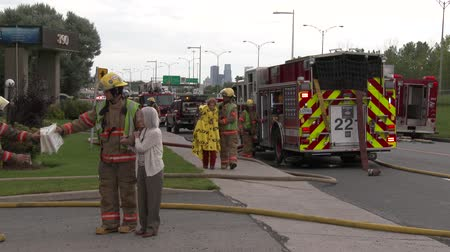 4K UHD - Firemen walking hand in hand with elderly women victims of fire