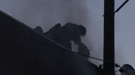 4K UHD - Silhouette of firemen cutting roof with circular saw with sparkles Stock Footage