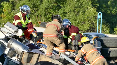 4K UHD - Firemen and paramedics holding injured truck driver on spinal board