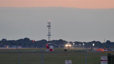 4K UHD - Large unidentifiable jet airplane landing at dusk