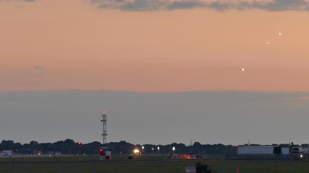 4K UHD - Planes lining up and landing at airport during sunset