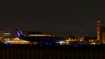4K UHD - Jumbo jet taxiing at night with airport terminal in background Stock Footage