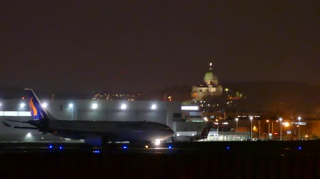 4K UHD - Airplane taxiing at night with historical church building Stock Footage