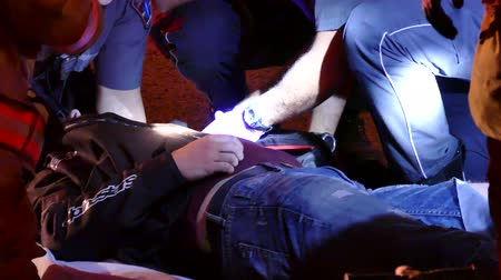 ambulância : 4K UHD - Paramedics cutting off unconscious patients clothes at night Stock Footage
