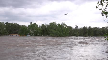 Army airplane flying above heavily flooded river with trailer and debris Stock Footage