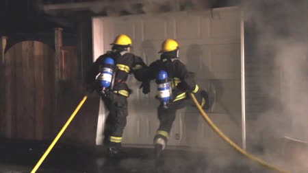 Two firemen kicking garage door simultaneously while trying to breach it