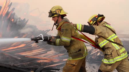 ar : Fireman pulls nozzle handle open and lets water out with flames in background