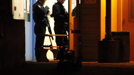 SWAT officers with shotgun looking at remote control police robot with lights