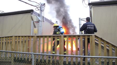 Firemen pull hose and shout bring the water while attending fire Stock Footage