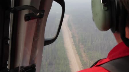Two helicopter pilots pointing and following dirt road while in flight