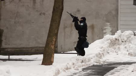Masked SWAT officer aiming riffle up high while walking backward
