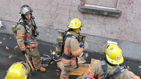 Aerial view of firemen opening up basement windows with smoke showing Stock Footage