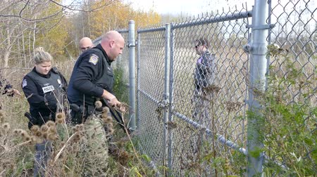 вводить : Police officers with tactical army pants cutting open a chain with bolt cutter
