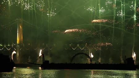 Green fireworks launching from floating platform on water with bridge Stock Footage