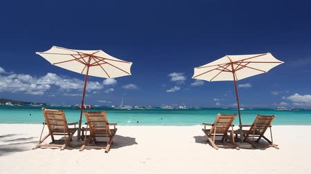 Мальдивы : Sun umbrellas and beach chairs on coastline with white sand