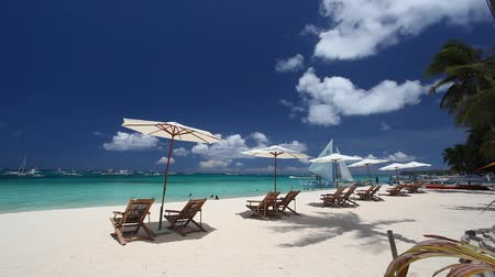 tourism : Sun umbrellas and beach chairs on coastline. Boracay, Philippines Stock Footage