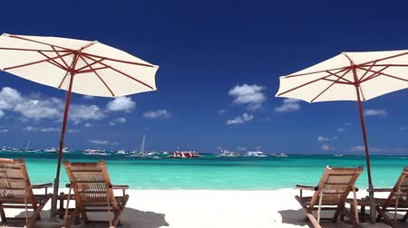 стулья : Sun umbrellas and beach chairs on coastline with white sand. Boracay, Philippines