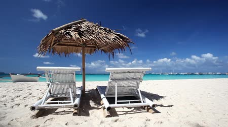 cadeira : Sun umbrella and two chaise longues on tropical beach with white sand Stock Footage