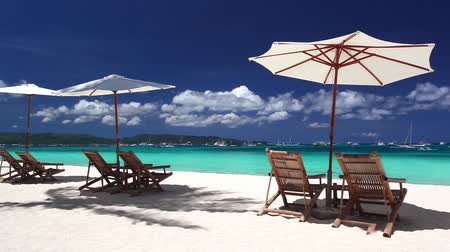 Мальдивы : Sun umbrellas and two chaise longues on tropical beach with white sand