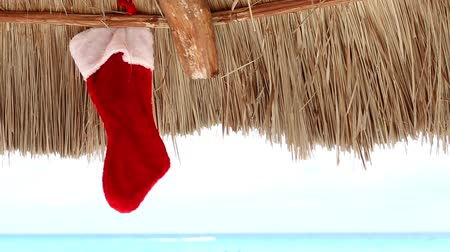ünnepies : Christmas sock on sun umbrella at caribbean beach. Holiday concept Stock mozgókép