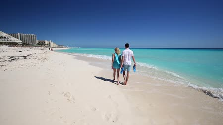 meksyk : Young couple with slippers walking  along the caribbean beach, Cancun, Mexico