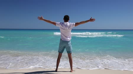 стоять : Young man standing on caribbean beach with outstretched hands, Cancun, Mexico Стоковые видеозаписи