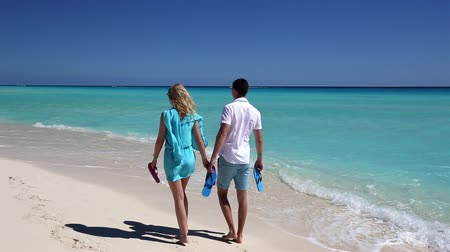 strand : Young couple with slippers walking  along the caribbean beach, Cancun, Mexico