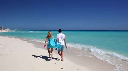 dominik : Young couple with slippers walking  along the caribbean beach, Cancun, Mexico