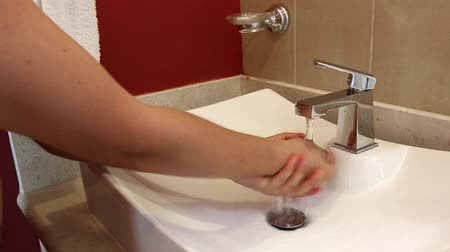 musluk : Man washes hands in bathroom sink, then turns water off