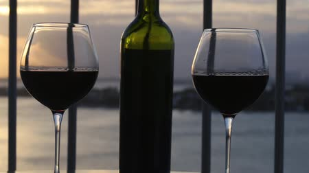 erkély : Two glasses and bottle with red wine on balcony overlooking at sunset