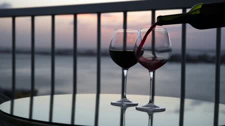 erkély : Pouring red wine in to glasses on balcony overlooking at sunset, slow motion