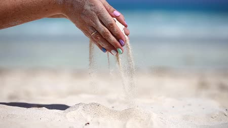 philosopher : Woman is pouring sand through her fingers on caribbean beach.