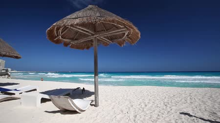 távozás : Caribbean beach with grass umbrellas and wooden beds. Vacation concept Stock mozgókép