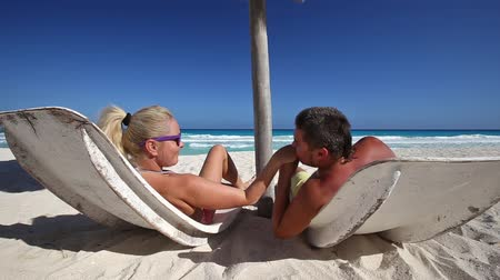 медовый месяц : Couple relaxing on beach. Looking on each other. Man take and kiss woman hand. Caribbean honeymoon. Enjoying life