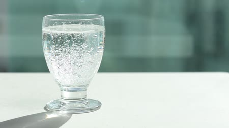 fizzing : Sparkling water in glass. Bubbles rising up and exploding