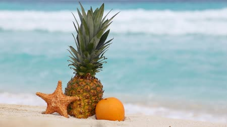 ananas : Pineapple, orange fruit and starfish on sand against turquoise caribbean sea water. Tropical summer vacation concept