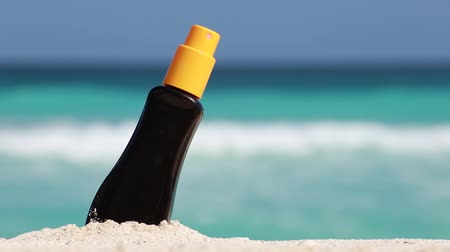skin brown : Sunscreen protection cream on white sand against turquoise caribbean sea water. Tropical summer vacation concept