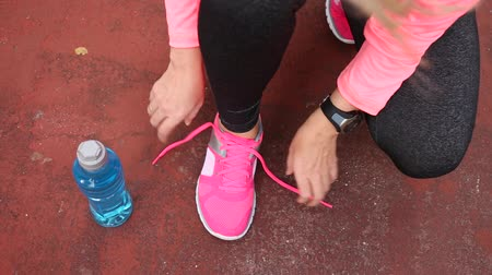 tying : Fitness woman tying running shoe laces, ready for jogging in summer park. Healthy lifestyle and sport concept Stock Footage