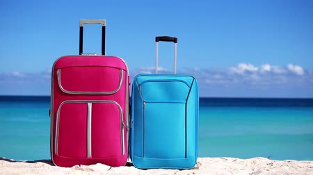 távozás : Two suitcases on sandy tropical beach. Vacation concept Stock mozgókép