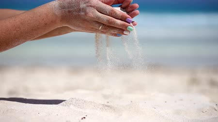 philosopher : Woman is pouring sand through her fingers