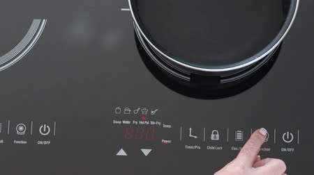 cooktop : Woman switch on Induction stove and set power of heating, closeup