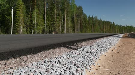 macadam : Unfinished asphalt country road in the forest Stock Footage